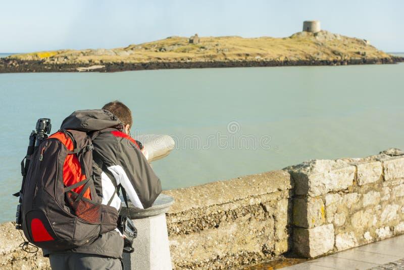 Mens die aan Dalkey-eiland door verrekijkers kijken stock afbeelding