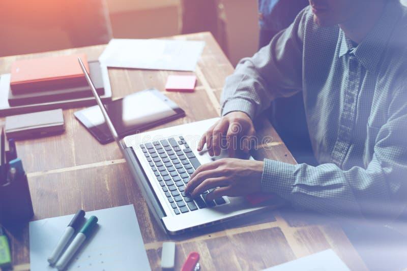 Mens die aan een project in open plekbureau werken Administratie en laptop op de lijst royalty-vrije stock foto's