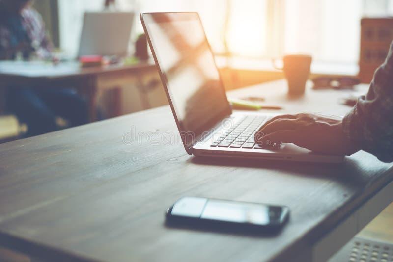 Mens die aan een project in open plekbureau werken Smartphone en laptop op de lijst royalty-vrije stock afbeelding