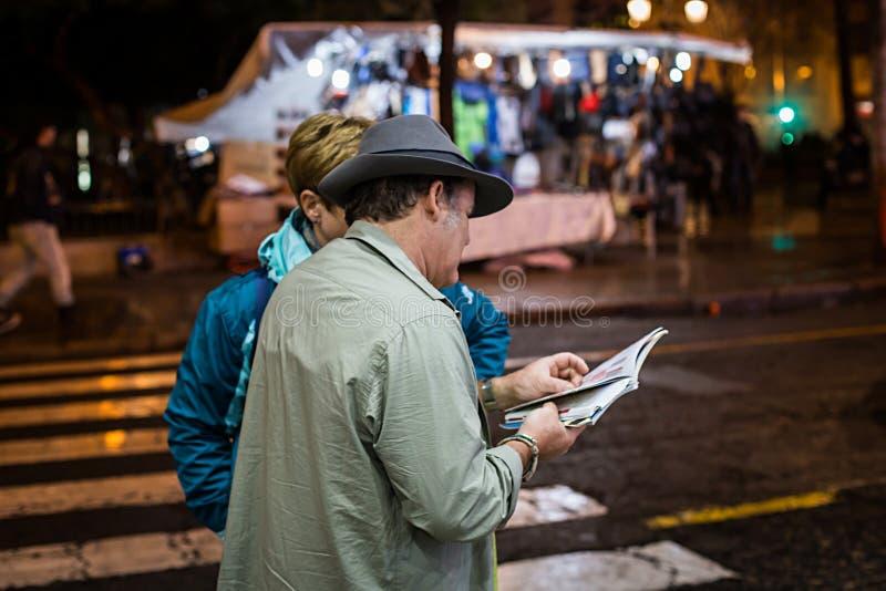 Mens die aan een toerist helpen een plaats in een document kaart op de straat te vinden stock foto