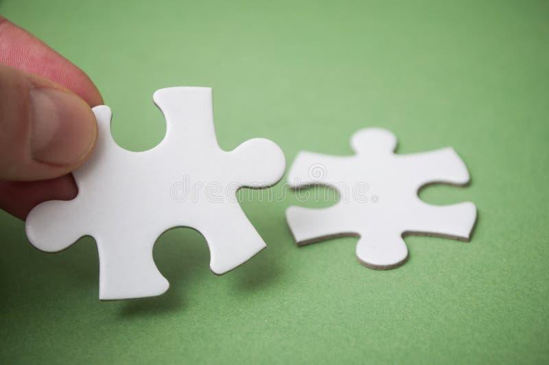 Mens die aan hand twee puzzelstukken op groene achtergrond verbinden Het concept het vinden van de juiste oplossingen in groepswe stock afbeeldingen