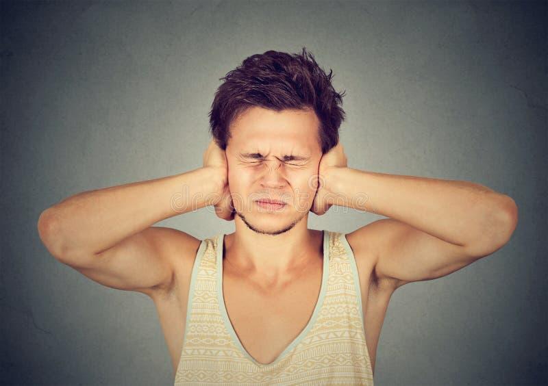 Mens die aan hevig lawaai lijden stock afbeeldingen