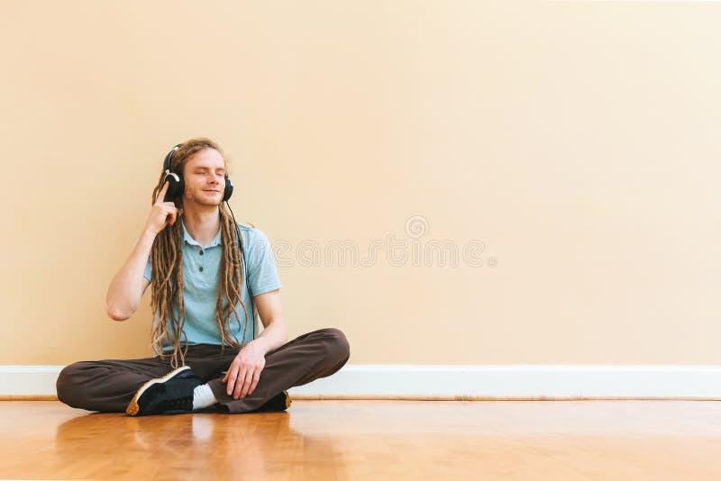 Mens die aan hoofdtelefoons in een grote ruimte luisteren stock fotografie