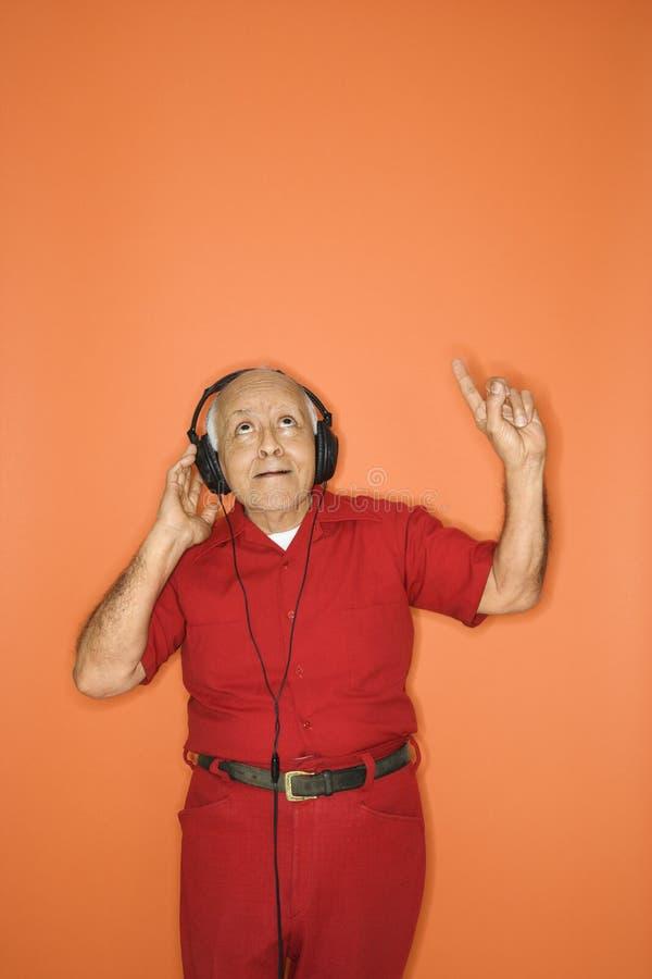Mens die aan hoofdtelefoons luistert. royalty-vrije stock fotografie