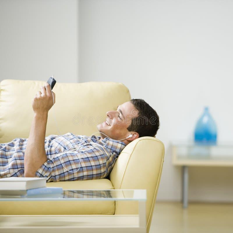Mens die aan hoofdtelefoons luistert stock foto's