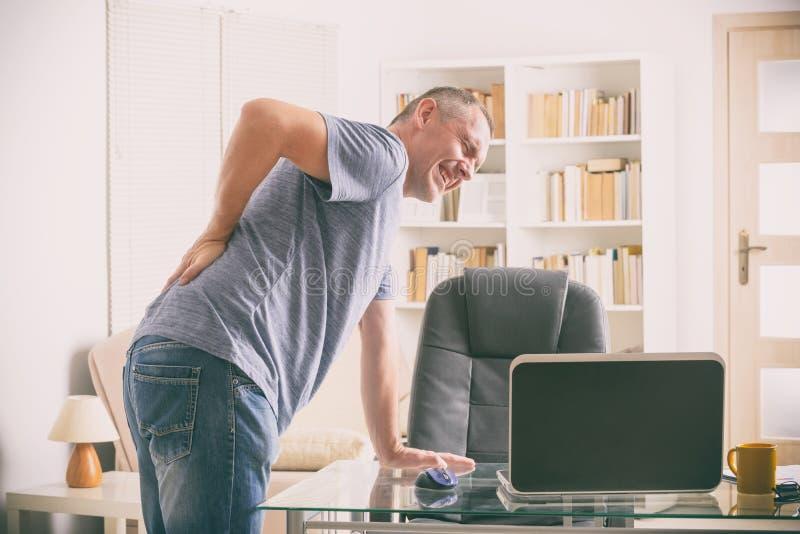 Mens die aan lage rugpijn lijden stock afbeeldingen