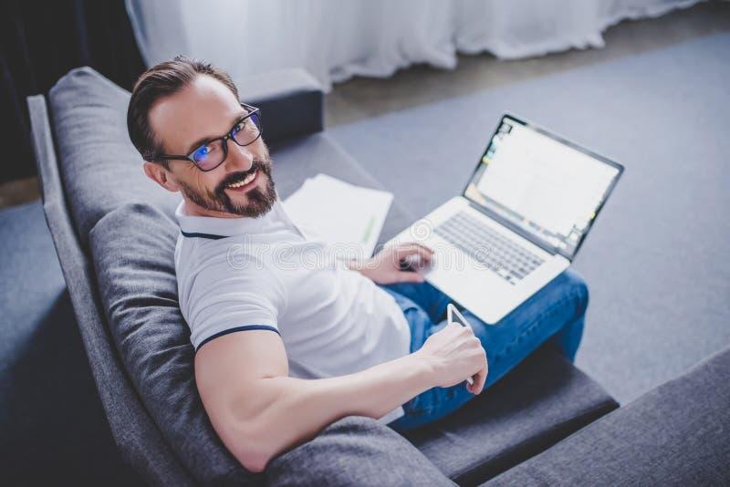 Mens die aan laptop thuis werkt royalty-vrije stock foto's
