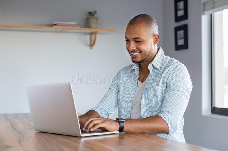 Mens die aan laptop thuis werkt royalty-vrije stock afbeeldingen