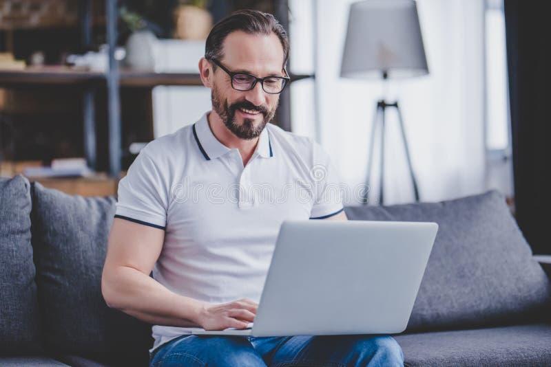 Mens die aan laptop werkt stock fotografie