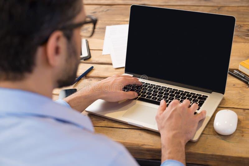 Mens die aan laptop werkt stock afbeeldingen