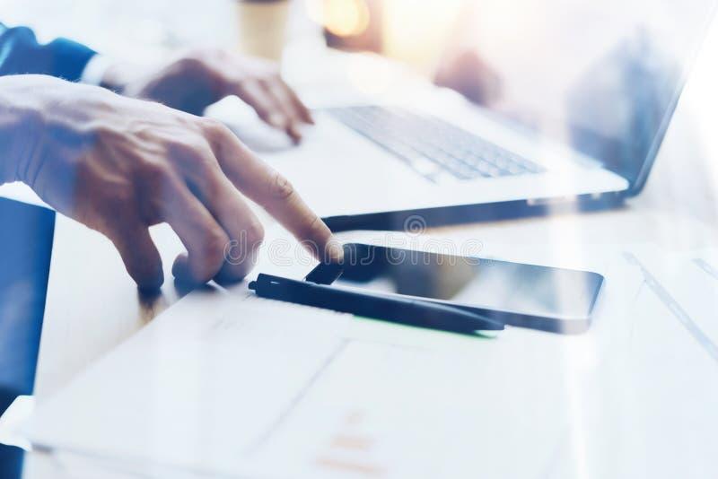Mens die aan moderne mobiele telefoon op kantoor werken en vinger richten aan huisknoop Horizontale vage close-upmening, stock afbeelding