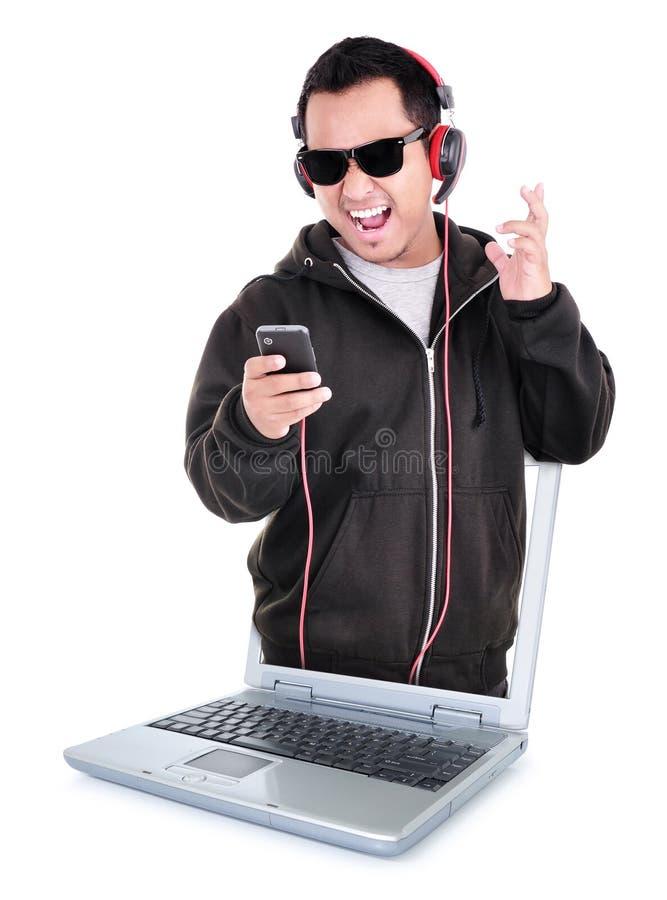 Mens die aan muziek en schreeuwen van binnenuit laptop luistert royalty-vrije stock foto