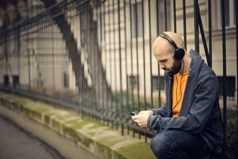 Mens die aan muziek luistert stock fotografie