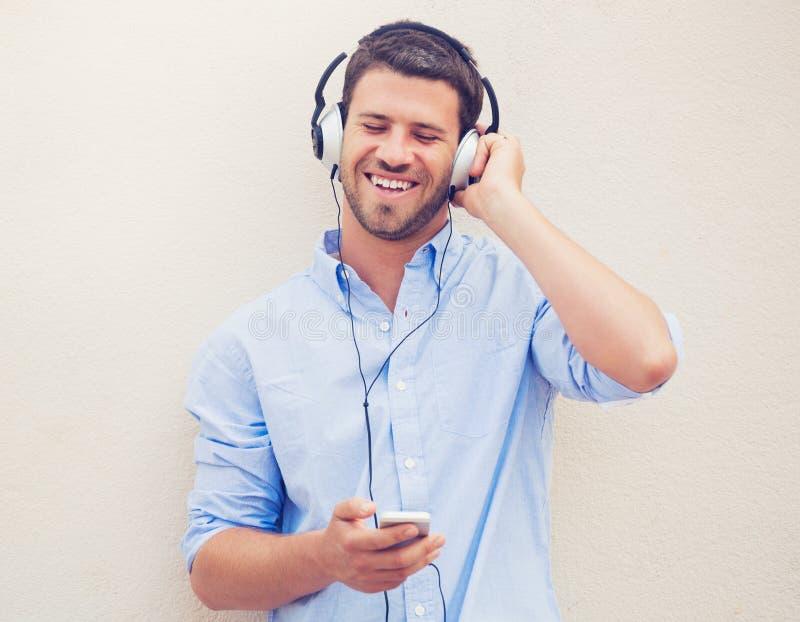 Mens die aan muziek met hoofdtelefoons luistert royalty-vrije stock fotografie