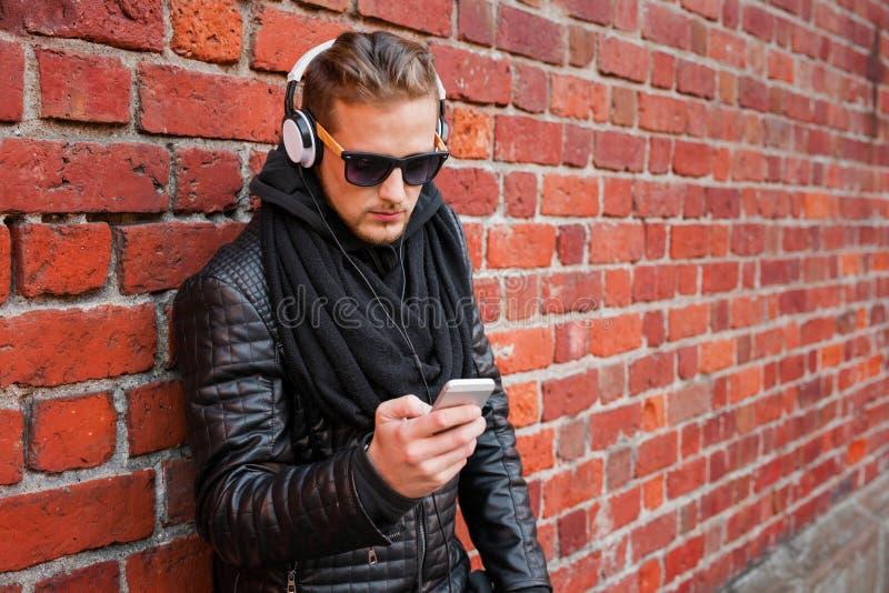 Mens die aan muziek op hoofdtelefoons van zijn smartphone luisteren royalty-vrije stock fotografie