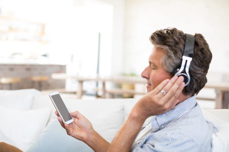 Mens die aan muziek op hoofdtelefoons in woonkamer luisteren royalty-vrije stock afbeeldingen