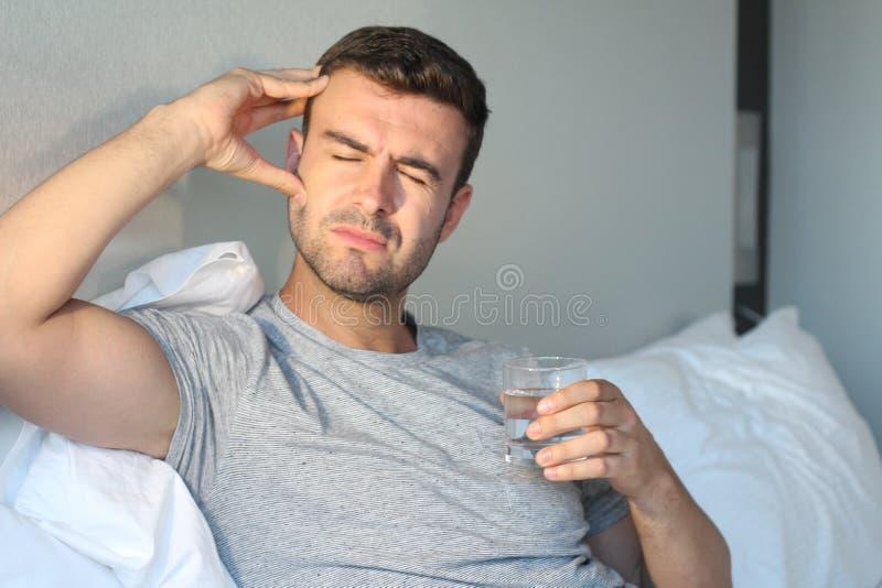 Mens die aan pijn in bed lijden stock fotografie