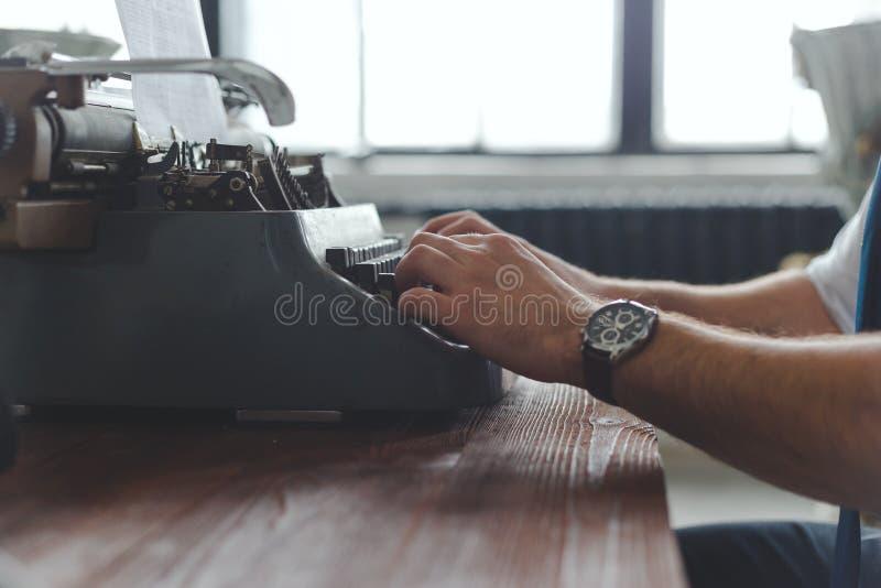 Mens die aan retro schrijfmachine bij bureau in woonkamerruimte werken royalty-vrije stock afbeelding