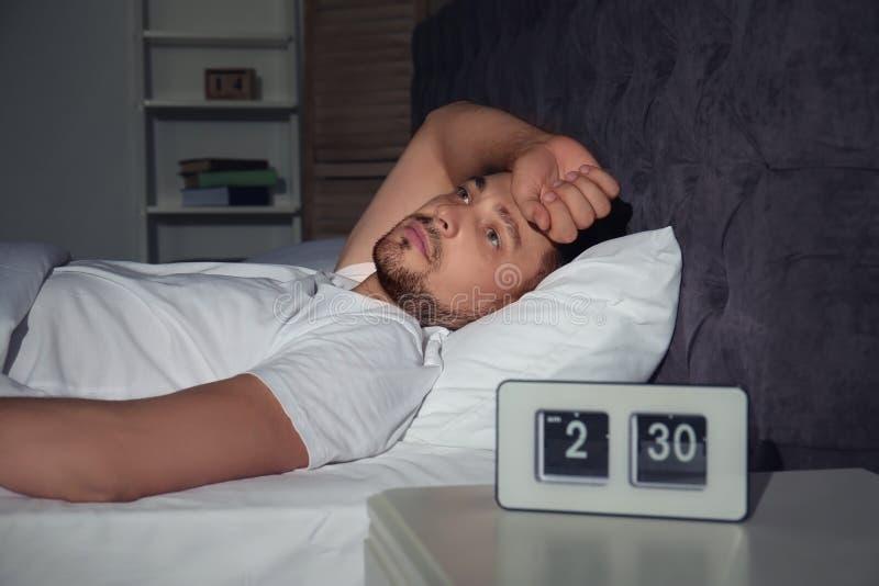 Mens die aan slapeloosheid in bed lijden stock afbeelding