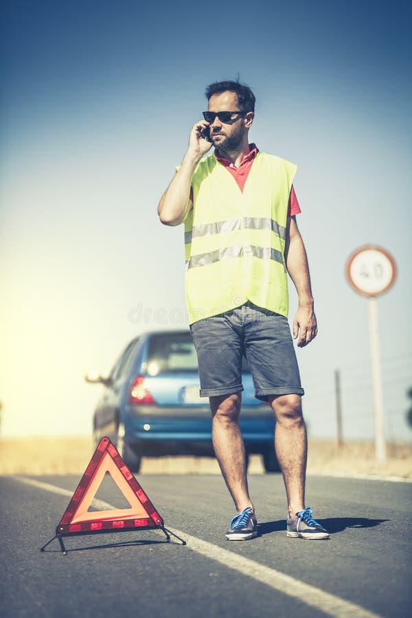 Mens die aan verzekeringsmaatschappij na een autoanalyse roepen stock foto