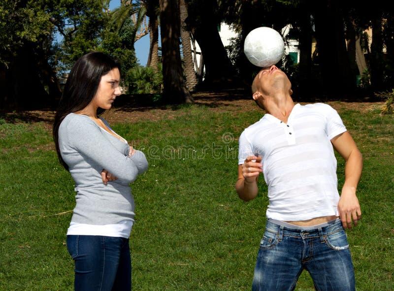 Mens die aan voetbal en meisjehaat het denkt royalty-vrije stock fotografie