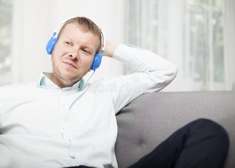 Mens die aan zich glimlachen aangezien hij aan muziek luistert stock afbeelding