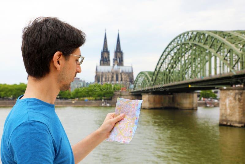 Mens die aan zijn document kaart in zijn hand met de Kathedraal van Keulen en brug op Rijn-rivier, Duitsland kijken Reis in Europ royalty-vrije stock foto