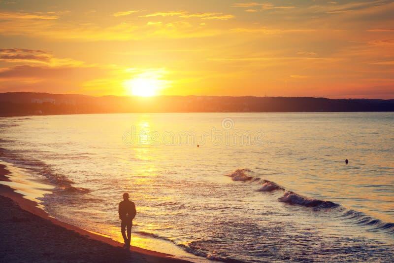 Mens die alleen op het strand bij zonsondergang lopen Kalme overzees royalty-vrije stock foto