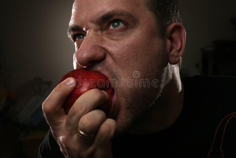 Mens die appel eet stock afbeeldingen
