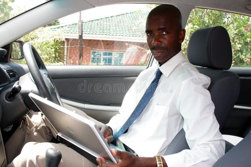 Mens die in auto werkt stock fotografie