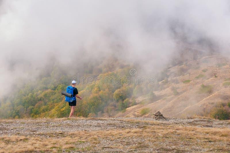 Mens die backpacker in de herfstbergen wandelen die mooi landschap bekijken stock afbeeldingen
