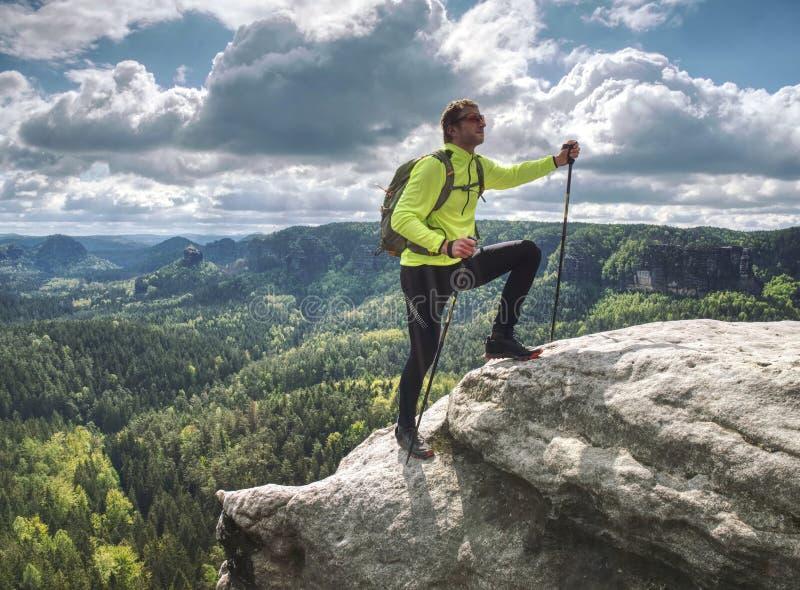 Mens die backpacker op rand van de berg de hoogste klip lanceert royalty-vrije stock fotografie