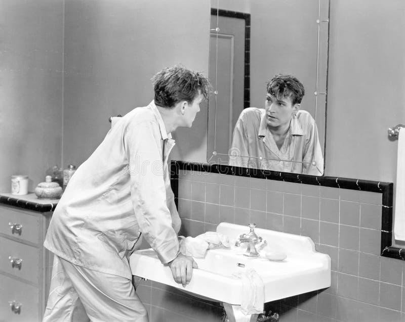 Mens die in badkamers spiegel onderzoeken (Alle afgeschilderde personen leven niet langer en geen landgoed bestaat Leveranciersga royalty-vrije stock foto's