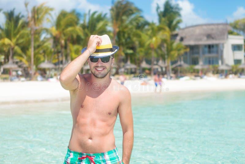 Mens die in badpak zijn hoed houden bij het strand royalty-vrije stock foto