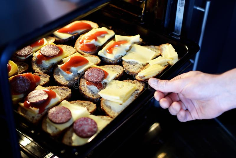Mens die bakseldienblad met plakken van roggebrood zetten met boter, kaas en salami in oven royalty-vrije stock afbeelding