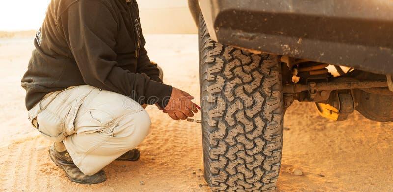 Mens die banddruk met meter meten Jeep 4x4 stock foto