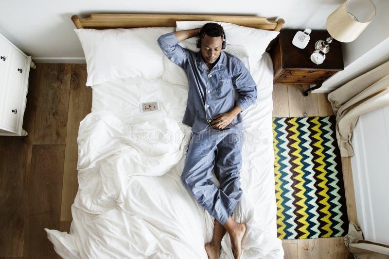 Mens Die In Bed Aan Muziek Luisteren Stock Foto - Afbeelding ...