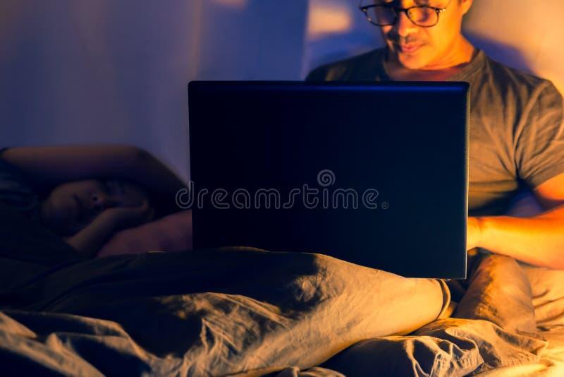 Mens die in bed liggen en met laptop laat bij nacht werken royalty-vrije stock foto's