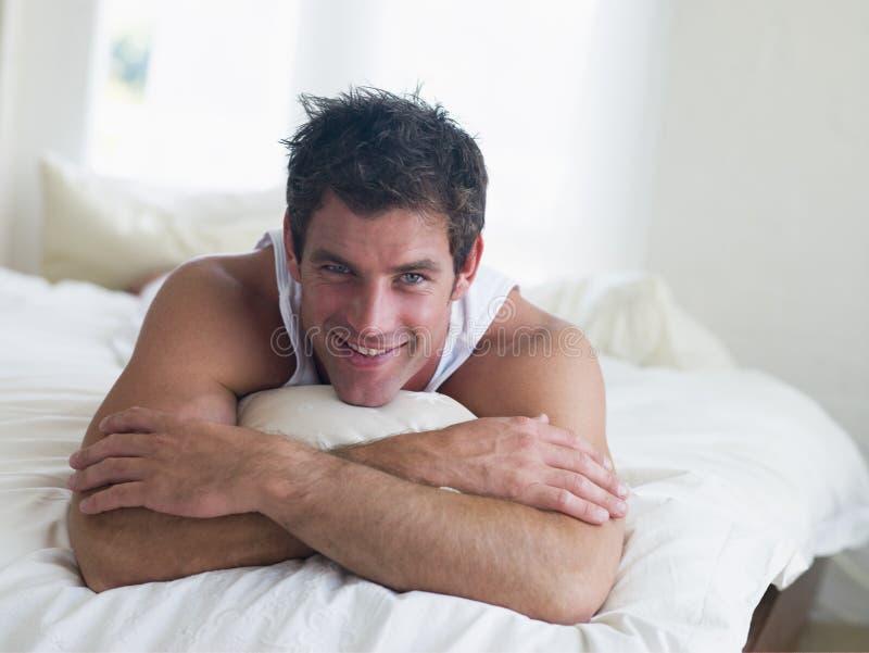 Mens die in bed ligt stock foto