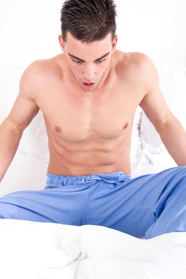 Mens die in bed zijn genitaal gebied bekijken die problemen hebben stock fotografie