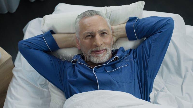 Mens die in bed zonnebaden die zich bij nieuwe orthopedische matras, comfortabele slaap verheugen stock fotografie