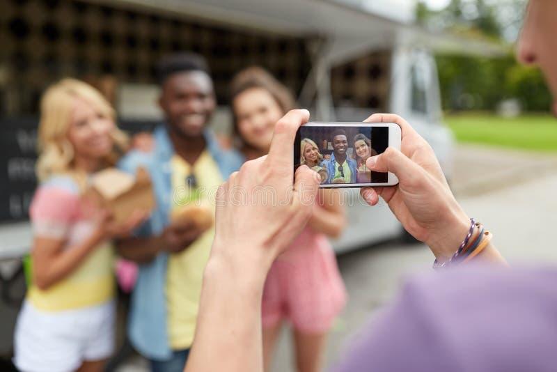 Mens die beeld van vrienden nemen die bij voedselvrachtwagen eten stock afbeelding