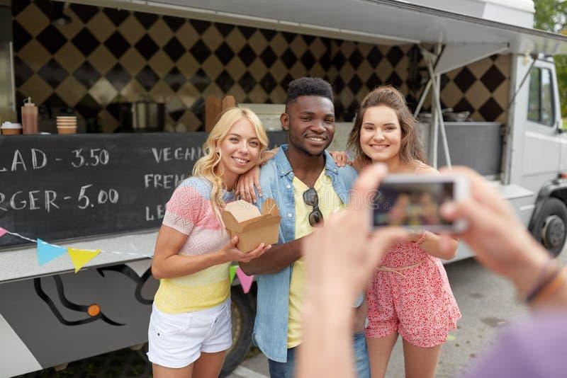 Mens die beeld van vrienden nemen die bij voedselvrachtwagen eten stock foto