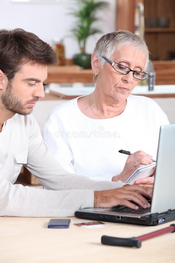 Mens die bejaarde dame helpt stock foto's