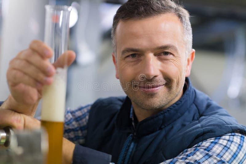 Mens die beker met bier in fabriek bekijken royalty-vrije stock afbeeldingen