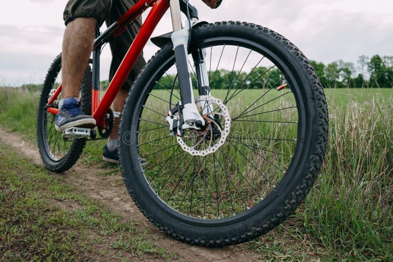 Mens die bereid om fiets bij de landweg te berijden worden royalty-vrije stock fotografie
