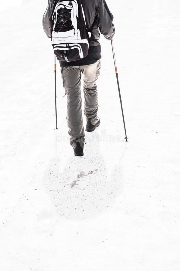 Mens die in bergen met sneeuw met wandelingsmateriaal 2 reizen stock foto's