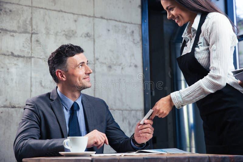 Download Mens Die Betaalpas Geven Aan Vrouwelijke Kelner Stock Foto - Afbeelding bestaande uit vrolijk, bank: 54082600