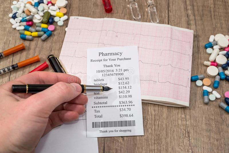 mens die bij apotheekontvangstbewijs tonen met rxspatie, pillen, spuit stock foto's