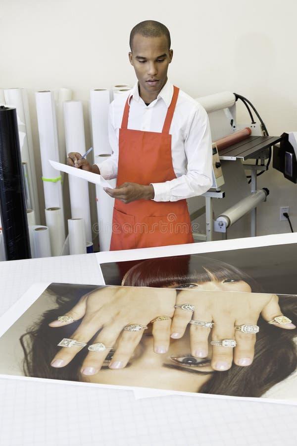 Mens die bij drukpers met fotoprintouts aan lijst werken stock foto's